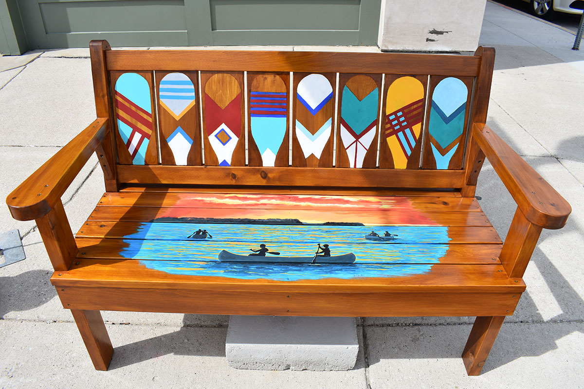 Bench with the paddles and kayaking scene.
