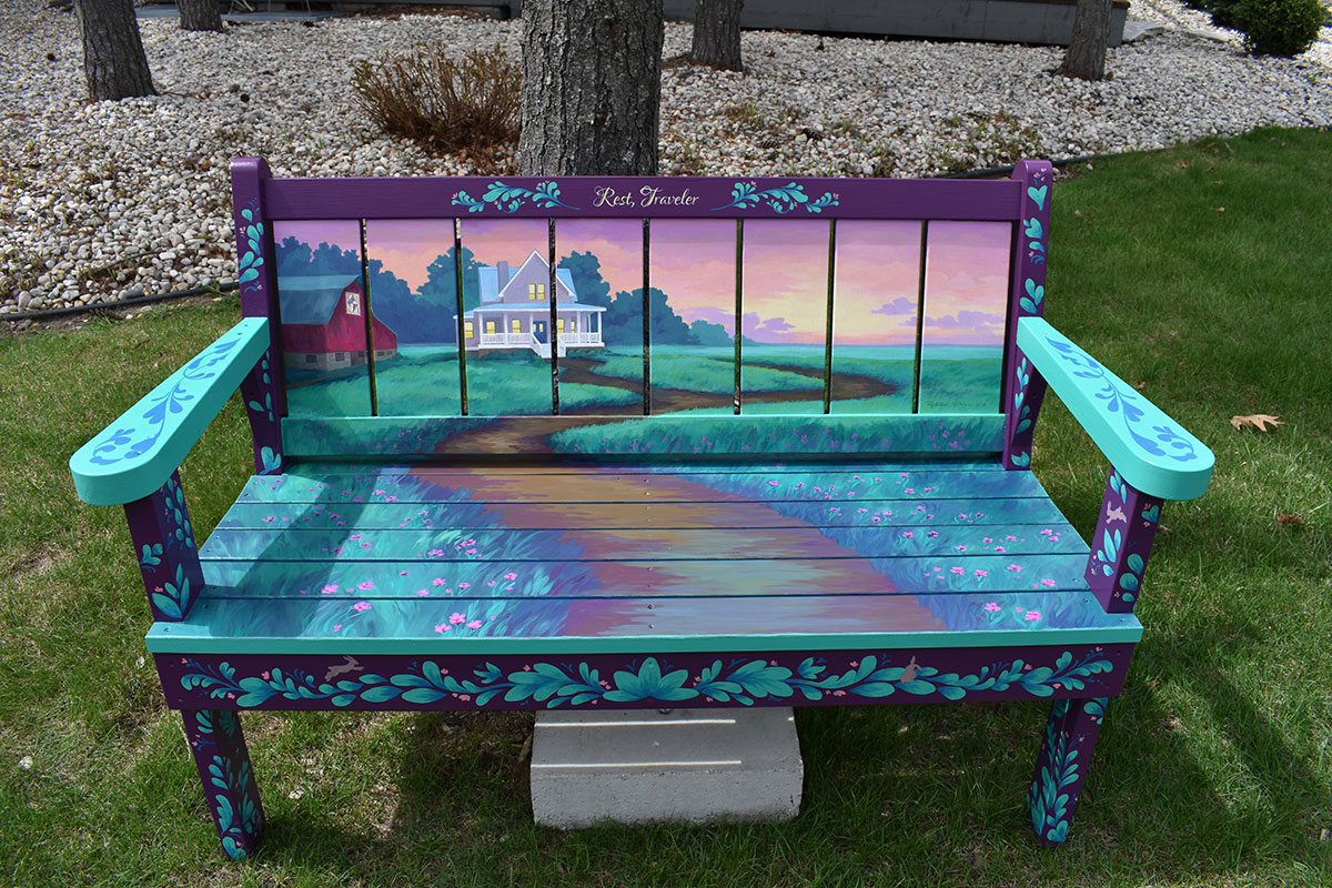 Bench with scene of house with wraparound porch and sunset in Sturgeon Bay, Door County.