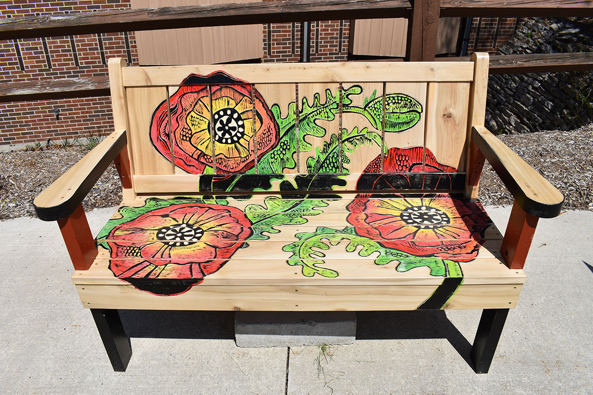 Bench displaying painting poppies in a garden in Sturgeon Bay, Door County.