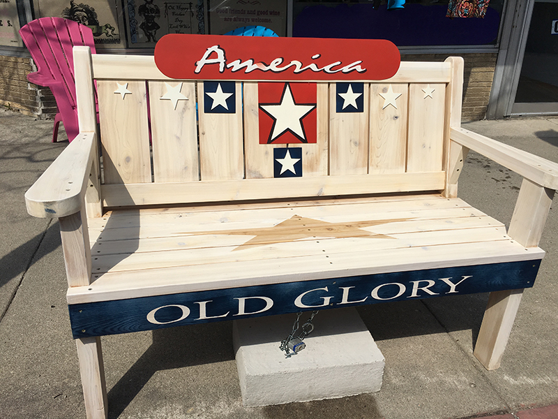 Bench painted with patriotic theme, including the word America and red white & blue stars, in Sturgeon Bay, Door County.