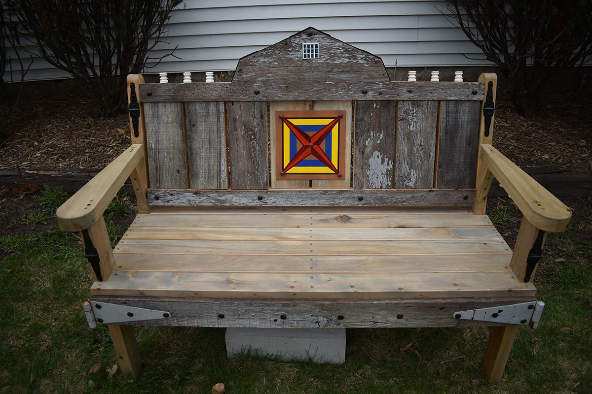 Bench decorated with barn quilt, barn boards and hinges.