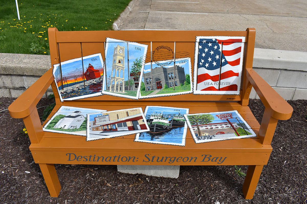 Bench decorated with stamps depicting Sturgeon Bay.