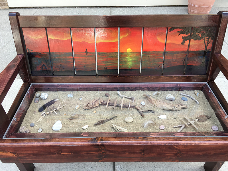 Bench painted with a sunset view and a glass seat with sand and beach items inset, in Sturgeon Bay, Door County.