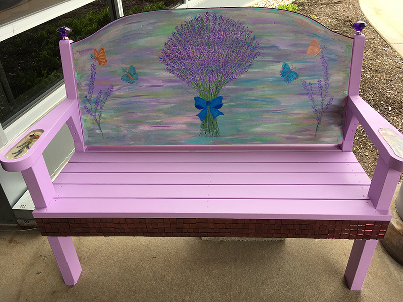 Lavender bench with flowers on the front and white tiles on the back in Sturgeon Bay, Door County.