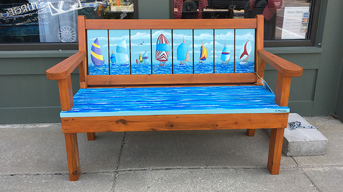 Bench displaying a painting of sail boats on the water in Sturgeon Bay, Door County.