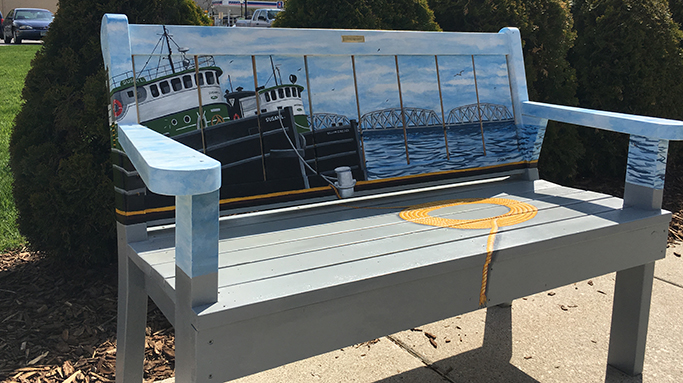 Bench painted with a tug boat in front of the bridge in Sturgeon Bay, Door County.