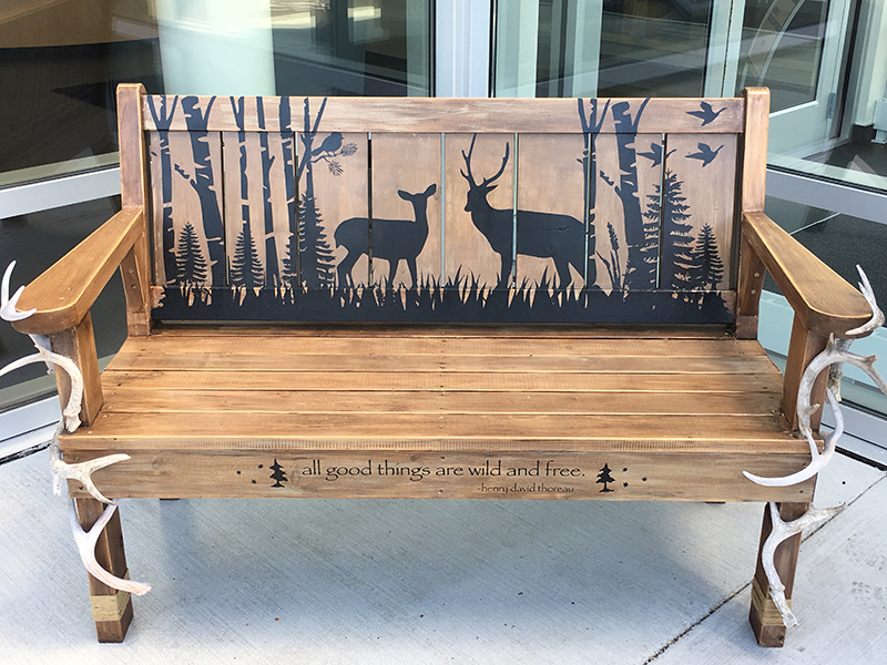 Bench painted with deer in trees, with antlers on the sides, in Sturgeon Bay, Door County.