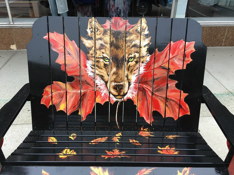 Bench painted with a wolf face coming through a maple leaf in Sturgeon Bay, Door County.