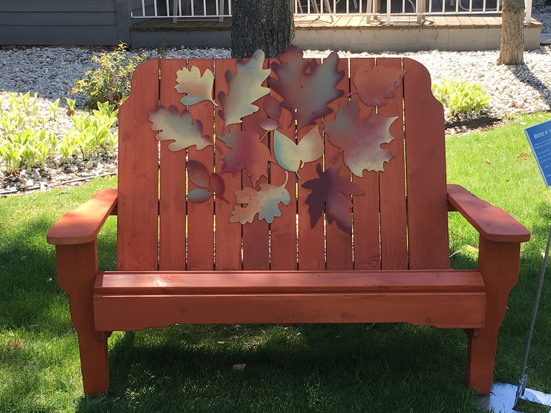 Brown bench decorated with autumn leaves in Sturgeon Bay, Door County.