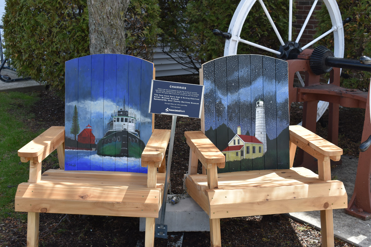 pair of chairs with hand painted seat backs depicting tug and lighthouse