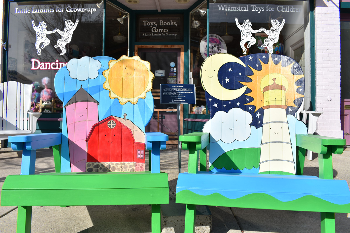 pair of adirondack chairs hand painted with barn and lighthouse scenes