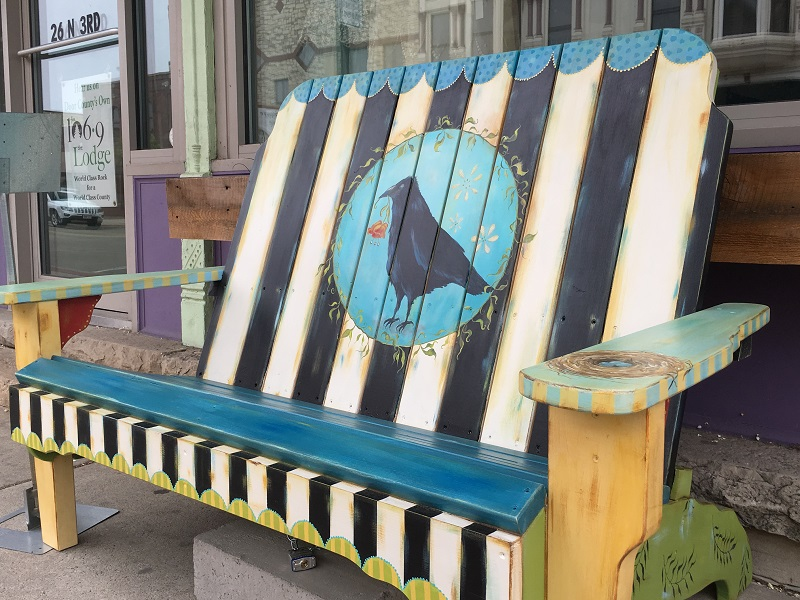 Bench decorated with a painting of a crow in Sturgeon Bay, Door County.