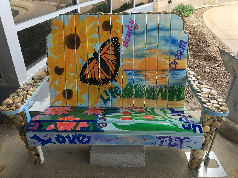Bench painted with butterflies, flowers, and beach scenery in Sturgeon Bay, Door County.