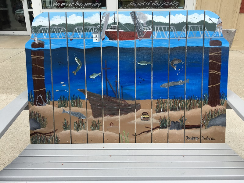 Bench displaying a painting of a ship crossing the open bridge, with underwater life below, in Sturgeon Bay, Door County.