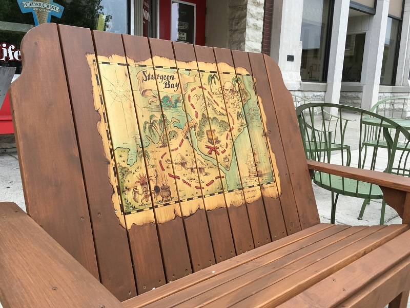 Wooden bench with a painted treasure map of Sturgeon bay in Door County.